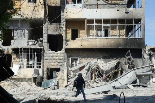 Cinegrafista corre em meio a uma rua bastante danificada pela guerra, em busca de cobertura, na cidade de Aleppo, Síria, 5 de outubro de 2012 [Tauseef Mustafa/AFP/Getty Images]