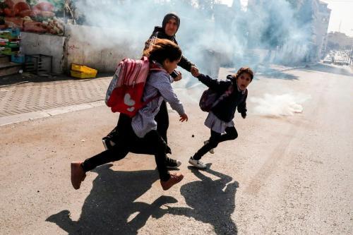 Uma mulher e duas meninas tentam fugir do gás lacrimogêneo disparado pelas forças israelenses em Cisjordânia em 17 de novembro de 2019 [Hazem Bader/ AFP/ Getty Images]