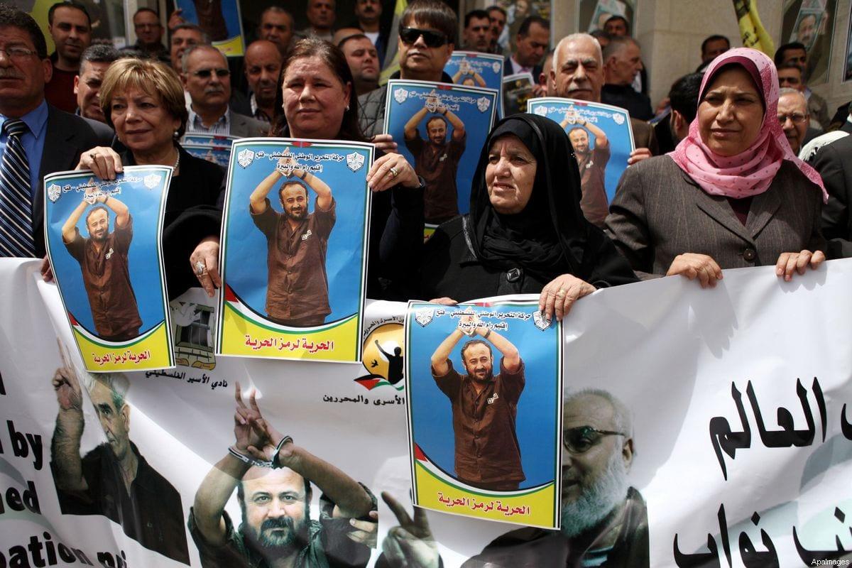 Palestinos mostram retratos do líder do Fatah, Marwan Barghouti, durante um protesto exigindo sua libertação da prisão israelense, em frente ao conselho legislativo palestino na cidade de Ramallah, na Cisjordânia, 15 de abril de 2015. [Shadi Hatem/ApaImages]