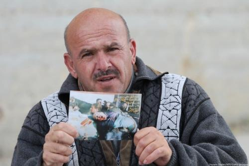 Mohammed Abu al-Halawa, um sobrevivente que ficou paraplégico após o massacre de 29 muçulmanos por um extremista judeu há 20 anos, posa com uma foto dele ferido em 25 de fevereiro de 2014, na cidade de Hebron, na Cisjordânia. [Hazem Bader/AFP/Getty Images]