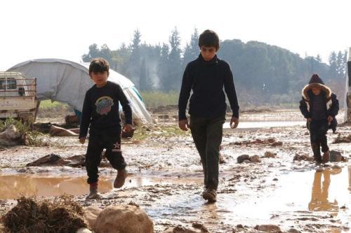 Crianças refugiadas tentam limpar suas tendas e casas após fortes chuvas inundarem o campo, em Afrin, noroeste da Síria, 31 de janeiro de 2021 [Muhammed Abdullah/Agência Anadolu]