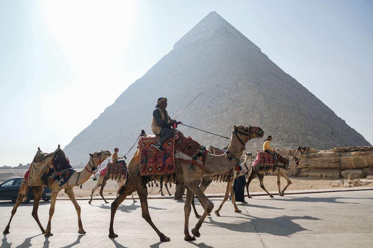 Camelos utilizados por turistas em frente à Pirâmide de Quéfren, na Necrópole de Gizé, Egito, 7 de janeiro de 2021 [Amir Makar/AFP via Getty Images]