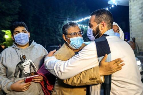 Mahmoud Hussein (C), um nacional egípcio e jornalista sênior da Al Jazeera árabe sediada no Catar, é abraçado por um homem ao chegar à casa de sua família na vila de Zawyet Abu Musallam em Gizé, cerca de 30 quilômetros ao sul da capital do Egito, Cairo, em 6 de fevereiro de 2021, após sua libertação da prisão. [AFP via Getty Images]