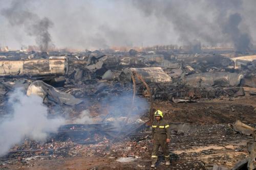 Um bombeiro caminha em meio a destroços de petroleiros após incêndio em Islam Qala, nos arredores de Herat, fronteira entre o Afeganistão e o Irã, em 14 de fevereiro de 2021. [HOSHANG HASHIMI/AFP via Getty Images]