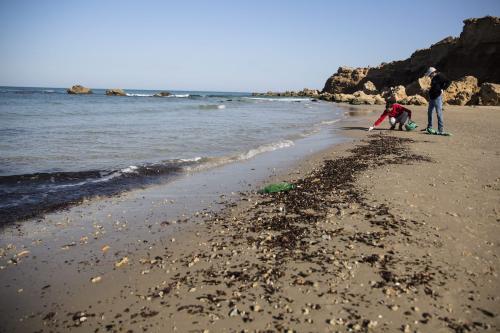 Voluntários limpam resíduos de petróleo da areia, como parte dos esforços de limpeza de uma praia em Hadera, litoral de Israel, em 22 de fevereiro de 2021 [Amir Levy/Getty Images]