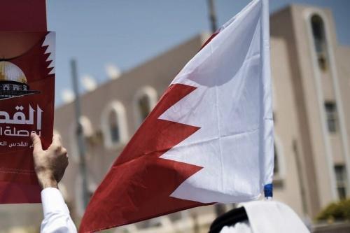 Homens do Bahrein erguem bandeira nacional. [Mohammed Al-Shaikh/AFP via Getty Images]