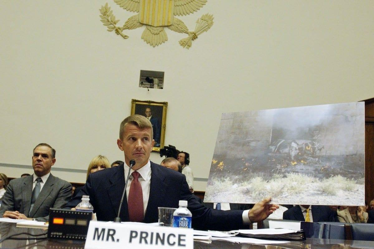 Erik Prince, presidente do Prince Group, LLC e Blackwater USA, mostra a foto de um SUV Blackwater atingido por um carro-bomba suicida em Mosul, Iraque, em 2005, como ele testemunhou durante uma audiência do Comitê de Supervisão da Câmara e Reforma do Governo no Capitólio em Washington, DC, contratação de segurança privada no Iraque e no Afeganistão em 2 de outubro de 2007 . [Bill Putnam / Bloomberg via Getty Images]