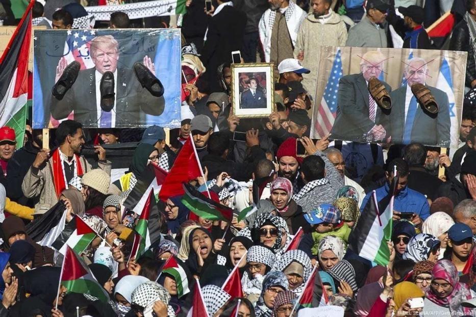 Manifestantes exibem bandeiras palestinas e marroquinas e retratos do então Presidente dos Estados Unidos Donald Trump e do Primeiro-Ministro de Israel Benjamin Netanyahu, com sapatos em seus rostos em sinal de repúdio, durante protesto em Rabat, Marrocos, 10 de dezembro de 2017 [Fadel Senna/AFP/Getty Images]