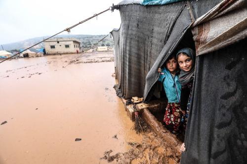Meninas refugiadas sírias olham de uma tenda em um campo de refugiados sírios após chuvas fortes causou inundações em Idlib, Síria em 17 de janeiro de 2021 [Agência İzzeddin İdilbi / Anadolu]