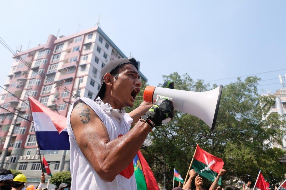 Manifestantes entoam palavras de ordem por trás de uma barricada, durante protesto contra o recente golpe militar, em Yangon, Mianmar, 27 de fevereiro de 2021 [Stringer/Agência Anadolu]