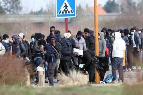 Migrantes irregulares são vistos enquanto esperam em uma fila para receber ajuda alimentar em Calais, França, em 25 de fevereiro de 2021. [Dursun Aydemir/Anadolu Agency]