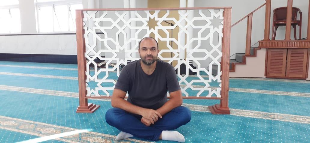 """Hani Hussein na mesquita com o """"divisor de ambiente"""" produzido por ele em MDF. [Foto arquivo pessoal]"""