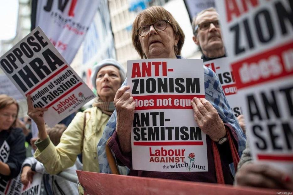 """Protestos em frente à sede da Executiva Nacional do Partido Trabalhista do Reino Unido, em Londres, Inglaterra, 4 de setembro de 2018; no cartaz: """"Antissionismo não equivale a antissemitismo"""" [Dan Kitwood/Getty Images]"""