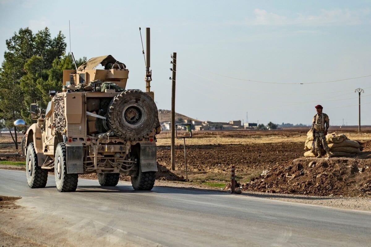 Combatente das Forças Democráticas Sírias (FDS) ao lado de uma estrada, enquanto passa um veículo militar dos Estados Unidos, a leste da cidade de Qamishli, sob gestão curda, no nordeste da Síria, em 13 de novembro de 2019 [Delil Souleimani/AFP via Getty Images]