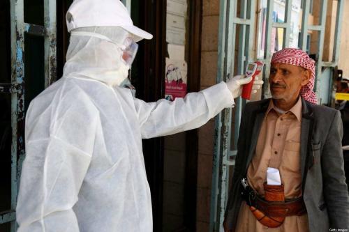 Profissional de saúde mede a temperatura de um homem como medida preventiva para combater o covid-19, em uma instalação pública em Sanaa, capital do Iêmen, 24 de março de 2020 [Mohammed Hamoud/Getty Images]
