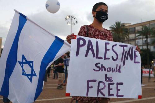 Um manifestante, usando uma máscara protetora devido à pandemia COVID-19, segura cartazes durante uma manifestação na Praça Rabin de Tel Aviv para denunciar o plano de Israel de anexar partes da Cisjordânia ocupada, em 23 de junho de 2020. [Jack Guez/ AFP via Getty Images]