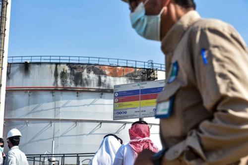 Homens olham para silo atingido por um ataque à instalação de petróleo Saudi Aramco na cidade de Jeddah no Mar Vermelho da Arábia Saudita em 24 de novembro de 2020 [Fayez Nureldine / AFP via Getty Images]