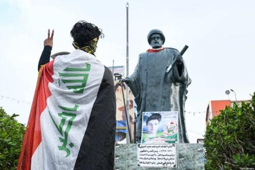 Jovem coberto com uma bandeira iraquiana faz o sinal de vitória em frente a uma estátua do poeta e clérigo Mohamed Said al-Habboubi, na praça batizada em sua homenagem, na cidade de Nassíria, sul do Iraque, 29 de novembro de 2020 [Asaad Niazi/AFP via Getty Images]