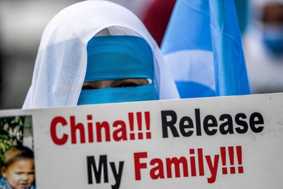 Membros da minoria de Mulheres Muçulmanas Uigures seguram cartazes e bandeiras em manifestação contra a China e seu tratamento à comunidade uigur na China, em 8 de março de 2021. [Ozan Kose/AFP via Getty Images]