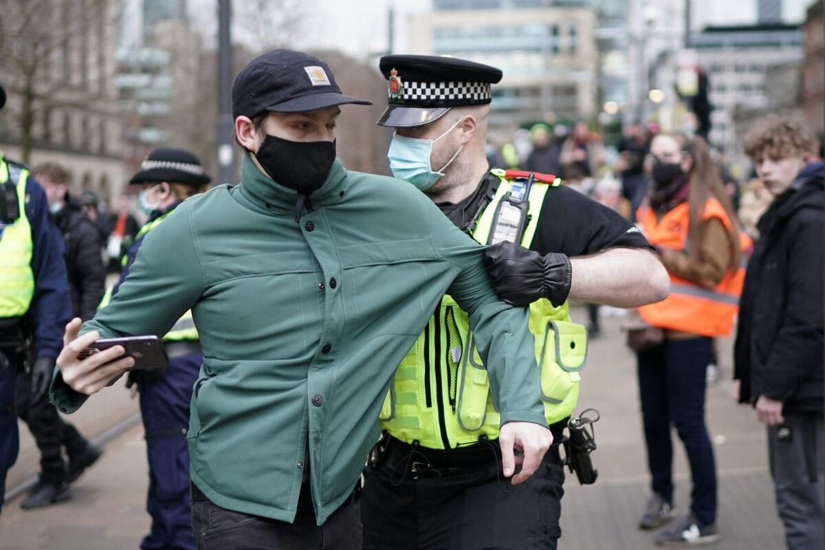 """Um manifestante é detido pela polícia após bloquear os trilhos do bonde durante um protesto """"Kill the Bill"""" no Manchester City Centre, em 27 de março de 2021, em Manchester, Reino Unido. [Christopher Furlong/Getty Images]"""