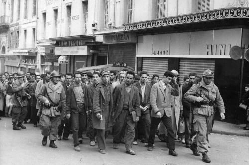 O exército francês prendeu muçulmanos que não conseguiram estabelecer sua identidade na Casbah, em Argel, para interrogatório. [Central Press/Getty Images]