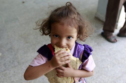 Uma criança iemenita deslocada, que fugiu da província de Saada com sua família devido aos combates entre rebeldes xiitas Huthi e forças leais ao exilado presidente do Iêmen, Abedrabbo Mansour Hadi, come pão em uma escola transformada em abrigo na capital Sanaa em 19 de agosto de 2015. [Mohammed Huwais/ AFP via Getty Images]