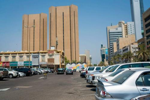 Automóveis parados em um estacionamento perto de lojas de varejo e torres de escritórios na Cidade do Kuwait, Kuwait, no domingo, 13 de agosto de 2017 [Tasneem Alsultan / Bloomberg via Getty Images]