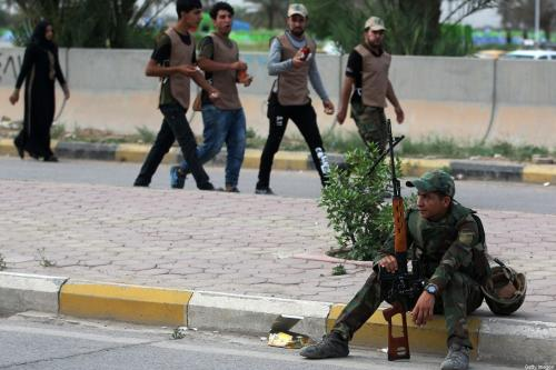 Um combatente iraquiano do Hashed al-Shaabi monitora durante uma reunião de campanha para a Aliança Fateh, uma coalizão de grupos milicianos apoiados pelo Irã, em Bagdá, em 7 de maio de 2018, antes das eleições parlamentares do Iraque a serem realizadas em 12 de maio. [Ahmad Al-Rubaye/AFP via Getty Images]