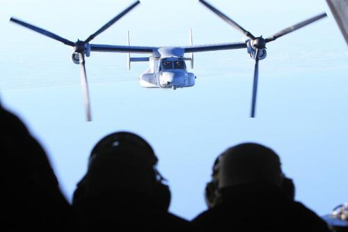 Fuzileiros navais observam uma aeronave MV-22B Osprey a caminho do USS Bataan, implantada em apoio à Operação Odyssey Dawn, em março de 2011. [Gisele Tellier/Getty Images]