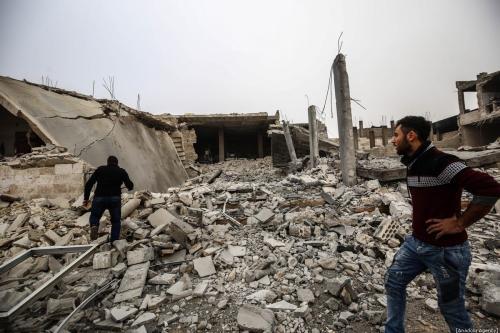 Sírios inspecionam destroços de edifícios depois que aviões de guerra pertencentes ao Regime de Assad atingiram Idlib, Síria, em 15 de dezembro de 2019 [İzzeddin İdilbi / Agência Anadolu]