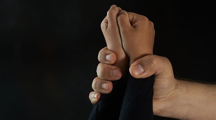 Violência infantil. A mão do homem segurando as mãos firmes da garota [Foto: Adobe Stock | Licenciado]