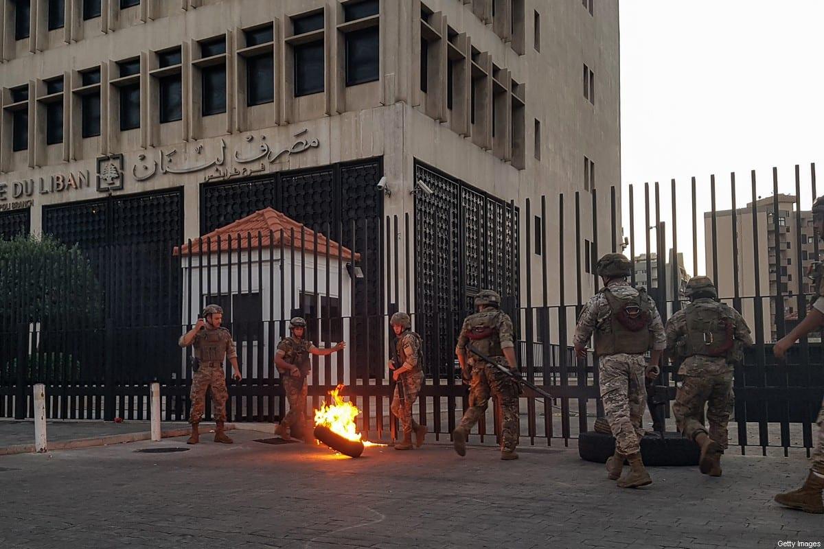 Soldados do Exército libanês tiram um pneu em chamas da cerca ao redor da filial local do Banque du Liban, enquanto os manifestantes se reúnem para protestar contra as péssimas condições econômicas na cidade de Trípoli, em 11 de junho de 2020 [Fathi Al-Marsi/AFP via Getty Images]