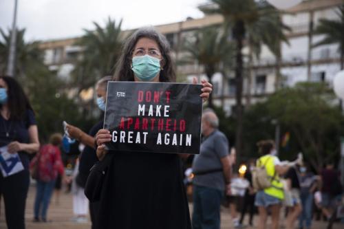 """Uma mulher israelense segura uma placa que diz """"Não faça o Apartheid Grande Novamente"""" enquanto ela protesta contra o plano do governo de Israel, em 23 de junho de 2020, em Tel Aviv, Israel [Amir Levy/Getty Images]"""