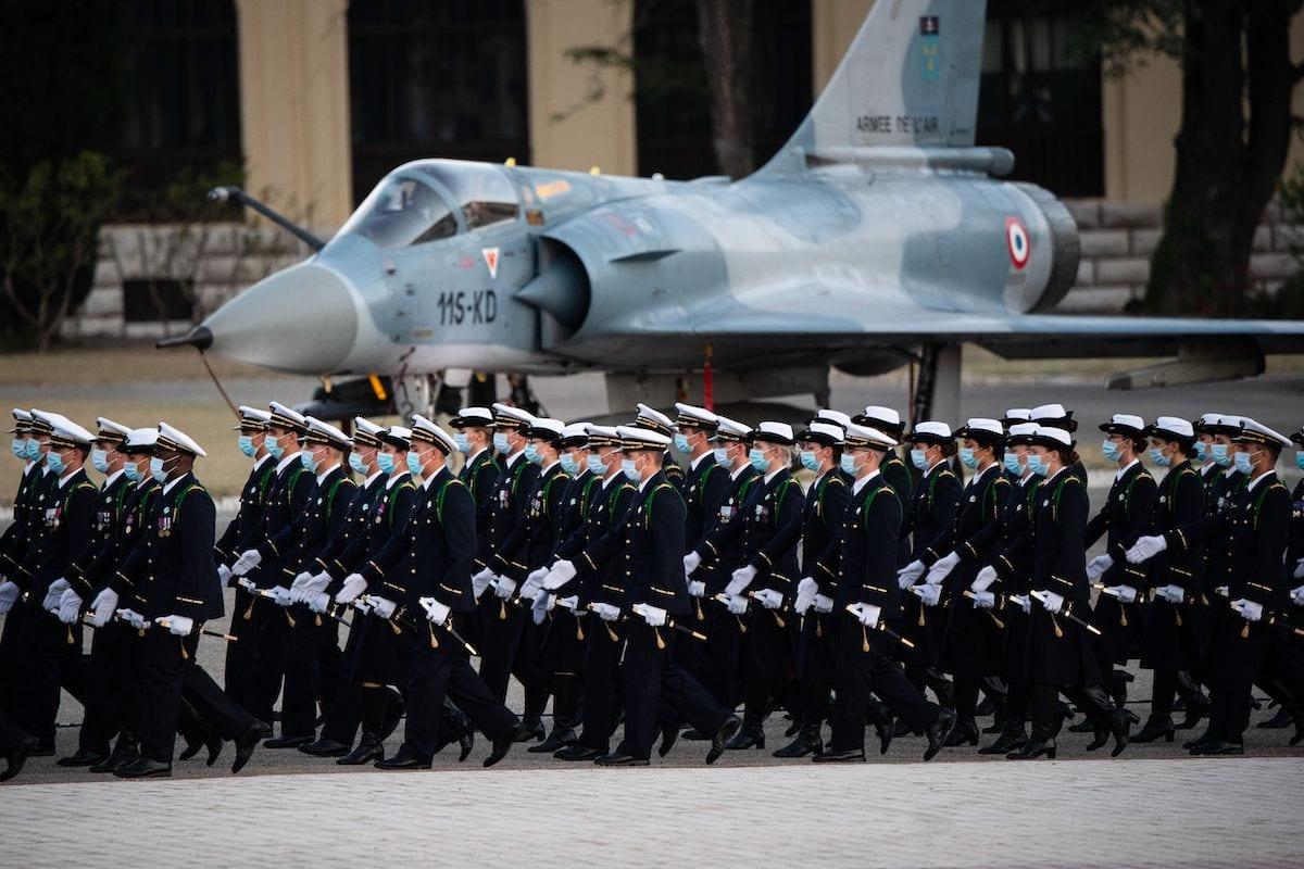Cerimônia de batismo de cadetes promovidos a oficiais da Air School. Eles desfilam com uso de máscaras, tento ao fundo um jato de combate Dassault Mirage 2000C da força aérea francesa durante sua no pátio da base aérea de Salon-de-Provence. Eem 24 de julho de 2020. [Clement Mahoudeau/ AFP via Getty Images]