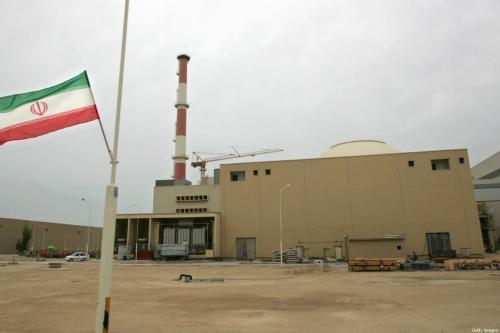 Foto de arquivo datada de 3 de abril de 2007 mostra uma bandeira iraniana fora do prédio que abriga o reator da usina nuclear de Bushehr na cidade portuária de Bushehr, no sul do Irã. [Behrouz Mehri/AFP FILES/AFP via Getty Images]