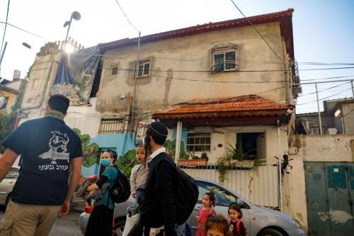 Colonos israelenses reúnem-se em frente a uma casa palestina, no bairro predominantemente árabe de Silwan, em Jerusalém Oriental ocupada, 9 de novembro de 2020 [Ahmad Gharabli/AFP via Getty Images]