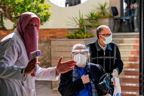 Um trabalhador médico egípcio verifica a temperatura das pessoas, em 4 de março de 2021, no Cairo [Khaled Desouki/AFP via Getty Images]