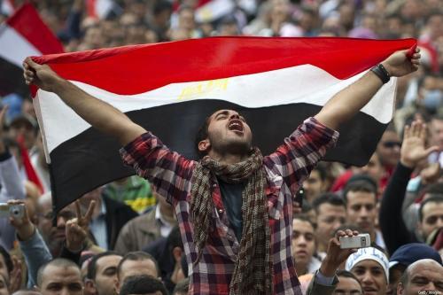 Um egípcio segura sua bandeira nacional enquanto profere mensagens contra o presidente Hosni Mubarak na Praça Tahrir, no Cairo, em 10 de fevereiro de 2011. [Pedro Ugarte/ AFP/Getty Images]