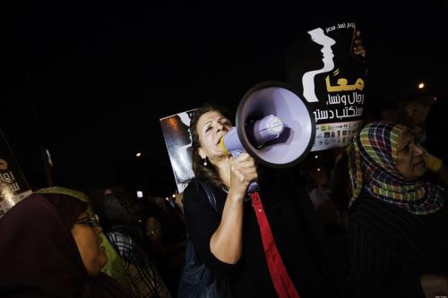 Mulheres e ativistas egípcias seguram slogans que dizem 'Juntos, homens e mulheres, escreveremos nossa constituição', em frente ao palácio presidencial no Cairo, em 4 de outubro de 2012 [Gianluigi Guercia/AFP/Getty Images]