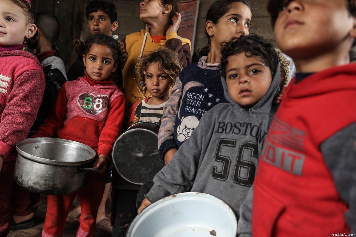 Crianças se reúnem para receber ajuda alimentar distribuída por uma benfeitora a famílias carentes no bairro de Zeitoun, na Cidade de Gaza, Gaza, em 28 de janeiro de 2021. [Ali Jadallah/Agência Anadolu]