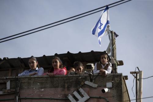 Crianças de uma família de colonos judeus observam um protesto de nativos palestinos no bairro de Sheikh Jarrah, em Jerusalém Oriental ocupada, 23 de abril de 2021 [Mostafa Alkharouf/Agência Anadolu]