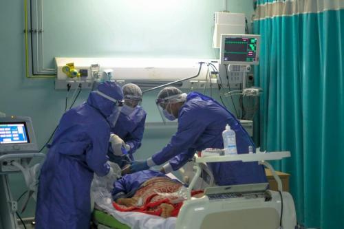 Equipe médica usando equipamento de proteção ajuda um paciente isolado enfermaria para o coronavírus no Cairo, Egito em 29 de abril de 2020 (COVID-19) [Ahya Diwer/ AFP/ Getty Images]