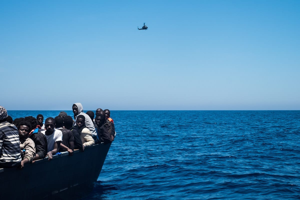 Refugiados esperam para embarcar no navio de resgate no Mar Mediterrâneo. Helicóptero líbio sobrevoa a área. Em 15 de junho de 2017 [Marcus Drinkwater/ Anadolu Agency]