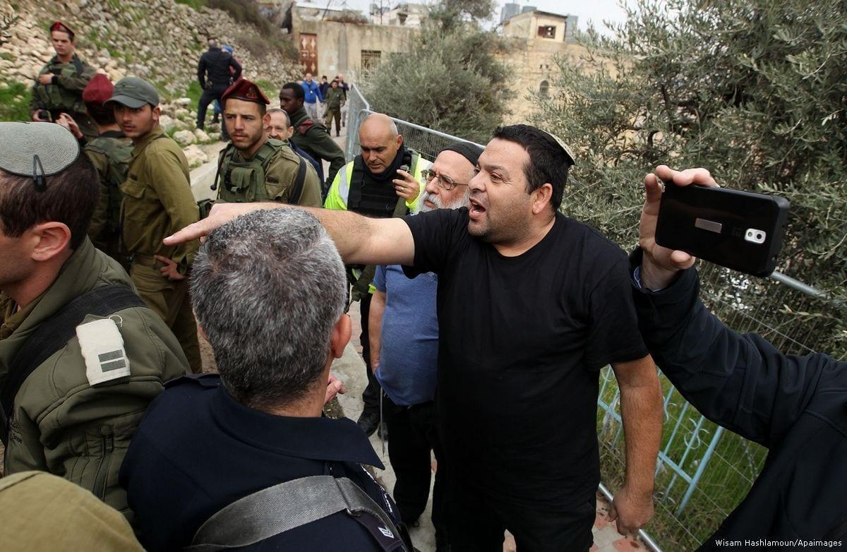 Forças israelenses estão na frente de colonos judeus que estão assediando palestinos na Cisjordânia [Wisam Hashlamoun/Apaimages]