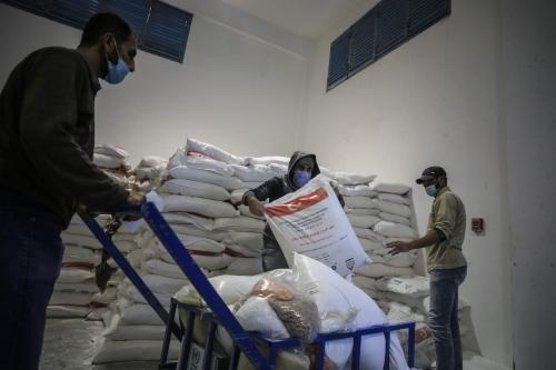 Trabalhadores da Agência das Nações Unidas de Assistência aos Refugiados da Palestina (UNRWA) organizam pacotes de ajuda humanitária de diversos países para distribuí-los em Jabalia, Faixa de Gaza, 17 de dezembro de 2020 [Ali Jadallah/Agência Anadolu]