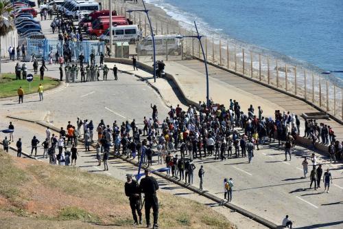 Forças de segurança marroquinas ficam de guarda enquanto os migrantes chegam para nadar no território espanhol de Ceuta na praia de Tarajal, em Fnideq, Marrocos, em 19 de maio de 2021. [Jalal Morchidi - Agência Anadolu]