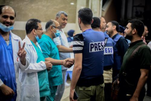 """Membros da imprensa palestina e profissionais de saúde se reúnem para uma celebração após o acordo de cessar-fogo """"mútuo e simultâneo"""" entre Israel e o Hamas que entrou em vigor às 2h da manhã de sexta-feira do horário local, encerrando o conflito de 11 dias, em Khan Yunis, Gaza, em 21 de maio 2021 [Abed Zagout/Agência Anadolu]"""