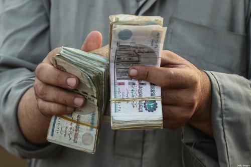 Um comerciante de gado egípcio conta seu dinheiro no mercado de Ashmun, na governadoria de Menufia, no Egito, em 15 de agosto de 2018 [Mohamed El-Shahed/AFP via Getty Images]