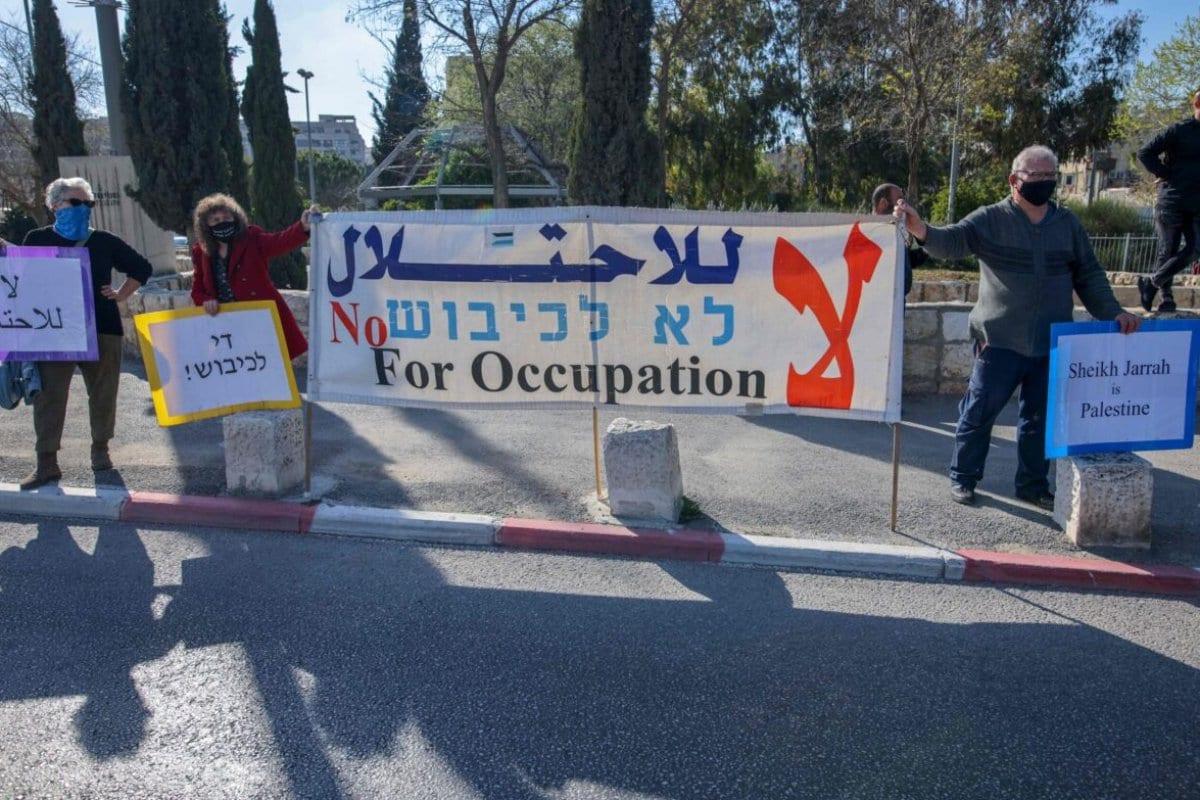 Ativistas palestinos, israelenses e estrangeiros erguem cartazes durante um protesto contra a ocupação e a expansão dos assentamentos ilegais de Israel no bairro de Sheikh Jarrah, em Jerusalém Oriental ocupada, 19 de março de 2021 [Ahmad Gharabli/AFP via Getty Images]