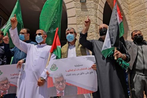 Apoiadores do movimento Hamas participam de comício contra a decisão da Autoridade Palestina de adiar as eleições legislativas e presidenciais marcadas para 22 de maio e 31 de julho, respectivamente, na Cidade de Gaza, 30 de abril de 2021 [Mahmud Hams/AFP via Getty Images]